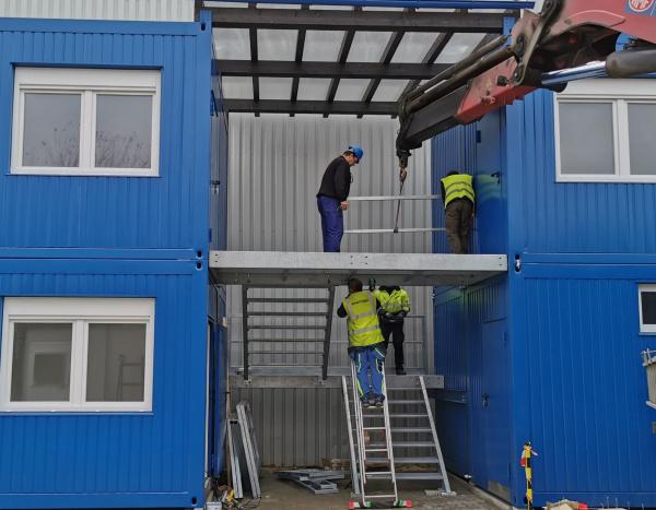Bureaux et conteneurs superposer avec escalier au milieu